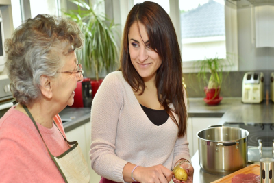 senior woman and caregiver cooking